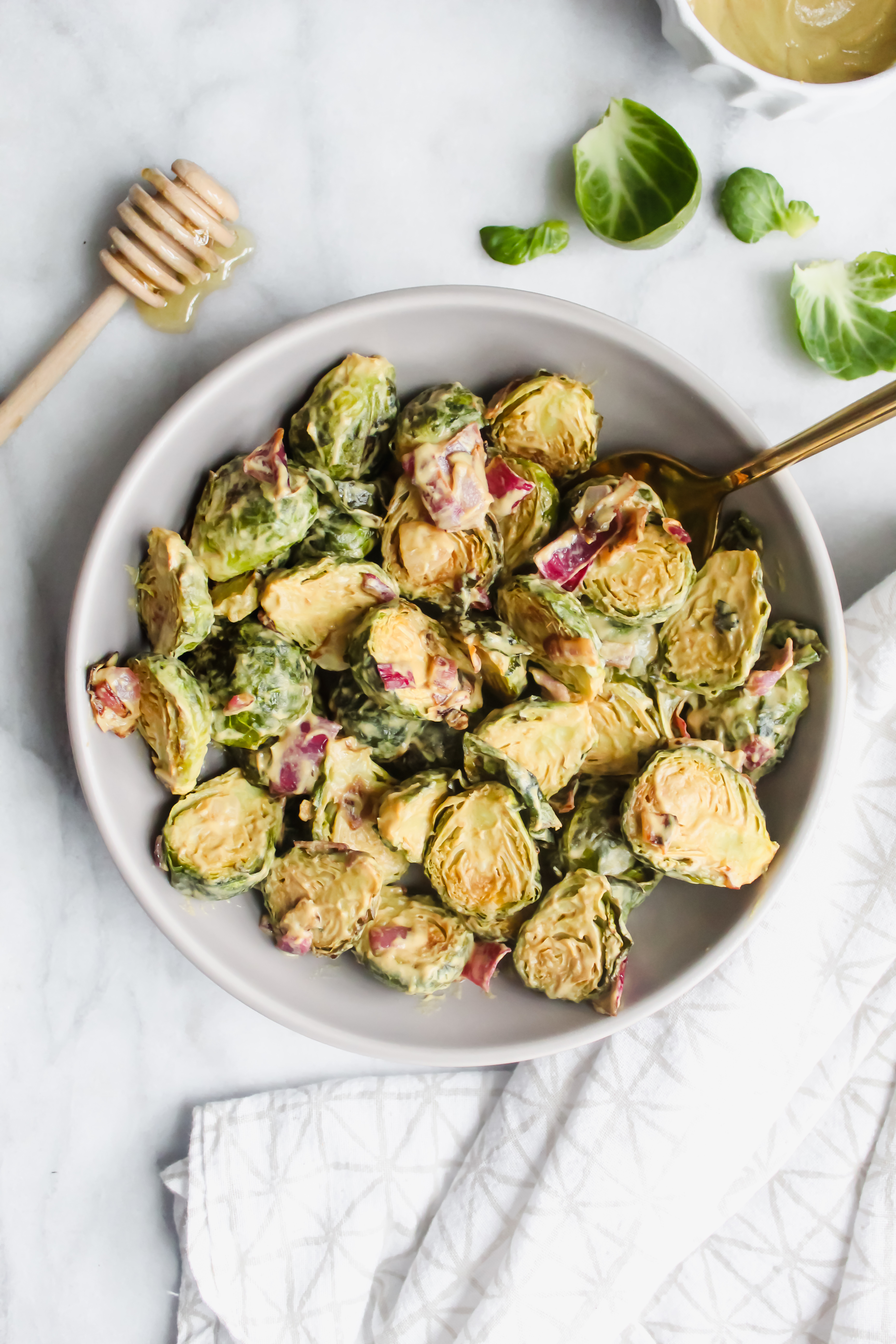 Honey Dijon Glazed Brussel Sprouts in a gray bowl with honey stick beside it