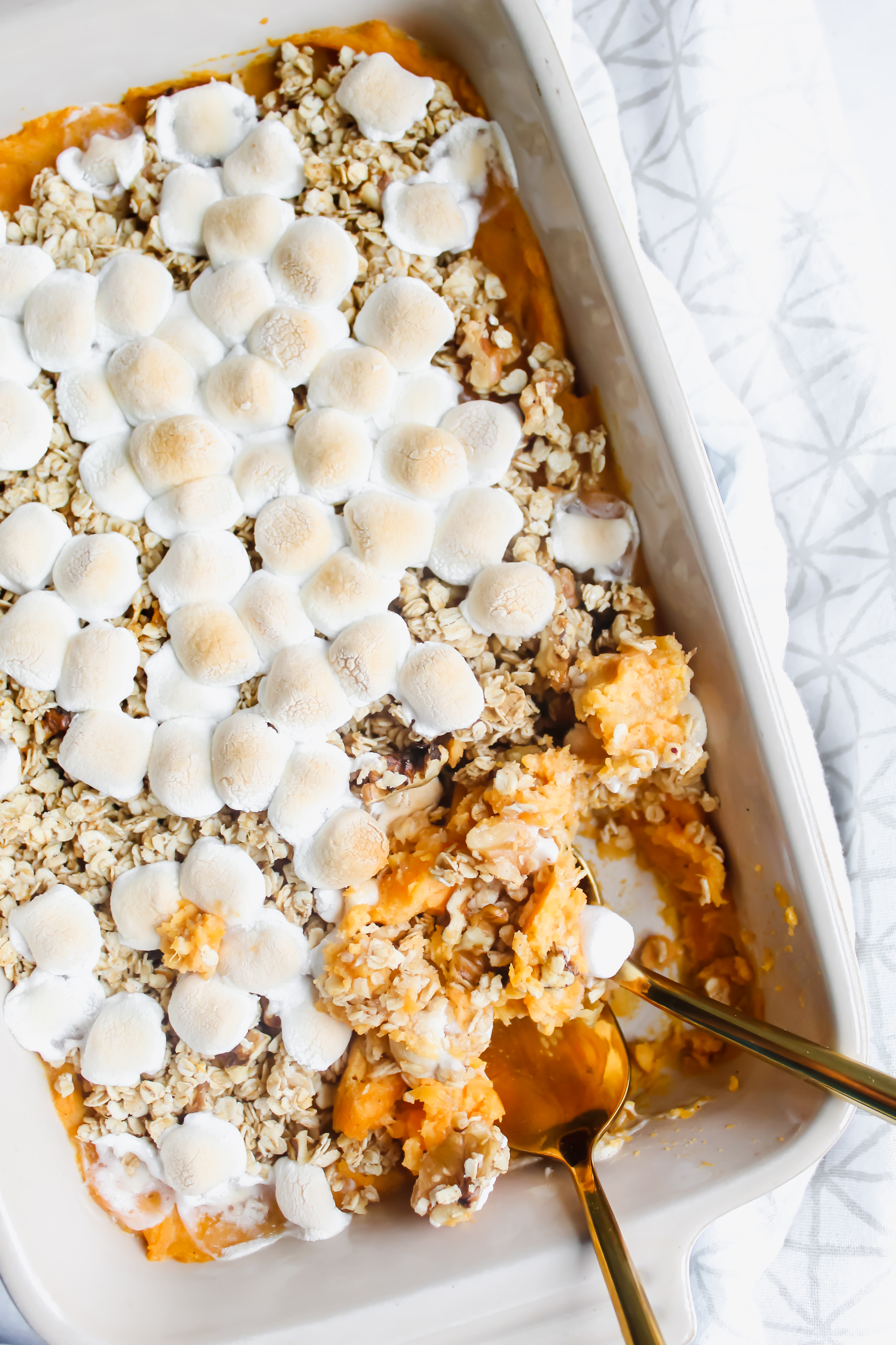 Healthy Sweet Potato Casserole with Maple Walnut Oat Topping in casserole dish with 2 golden spoons
