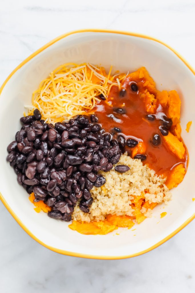 enchilada sauce, quinoa, black beans and cheese in a bowl