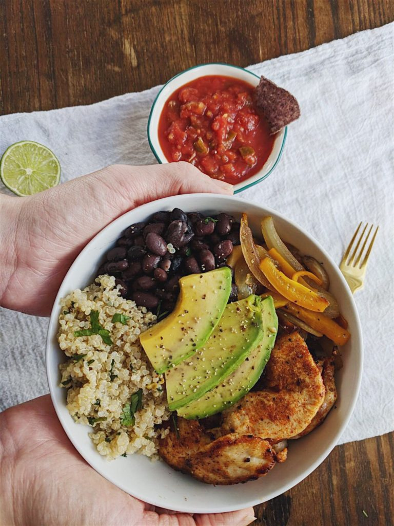 Healthy Spicy Chicken Burrito Bowls holding the bowl