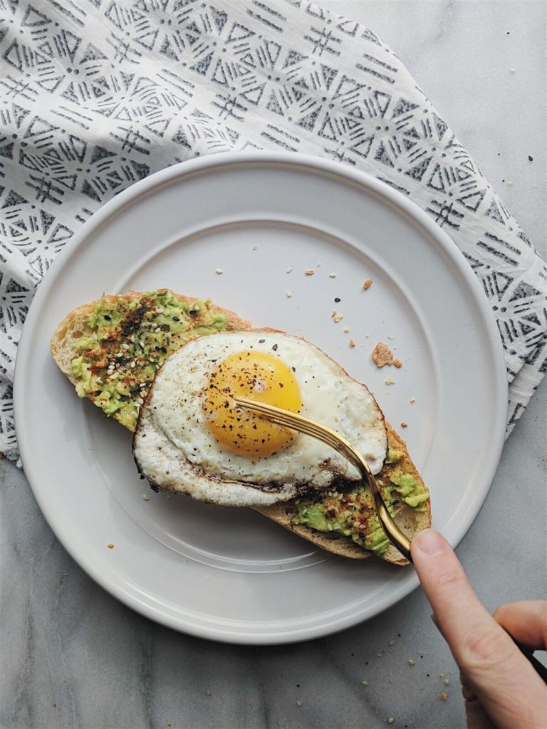 everything but the bagel avocado toast with fork dipping into the yolk