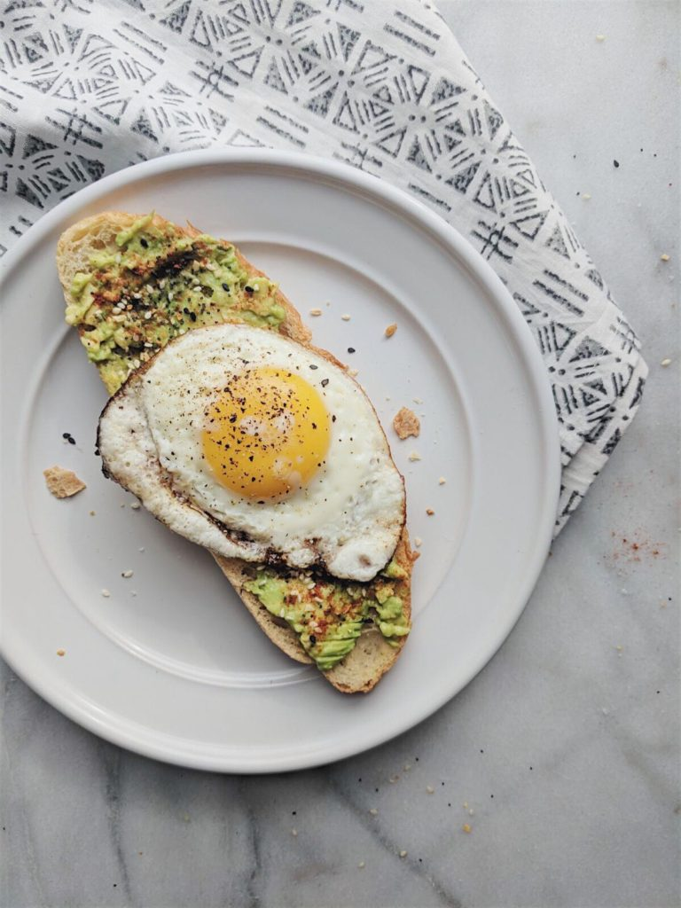everything but the bagel avocado toast on white plate with egg on top