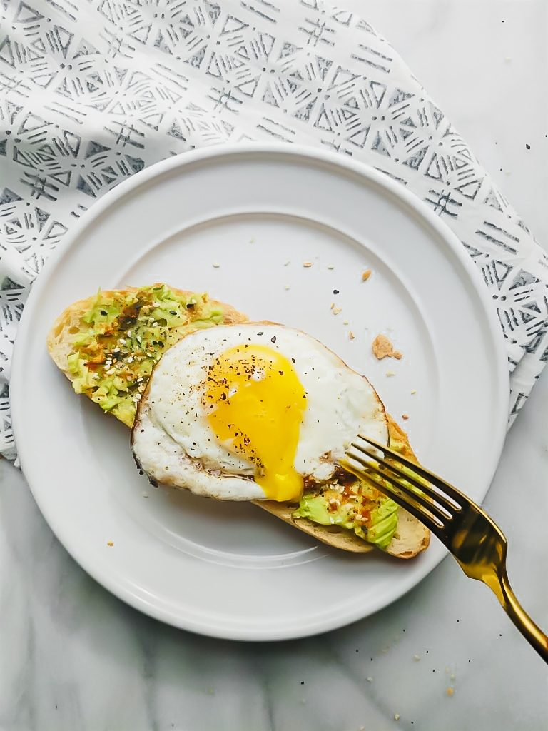 Everything but the Bagel Avocado Toast runny egg yolk on white plate