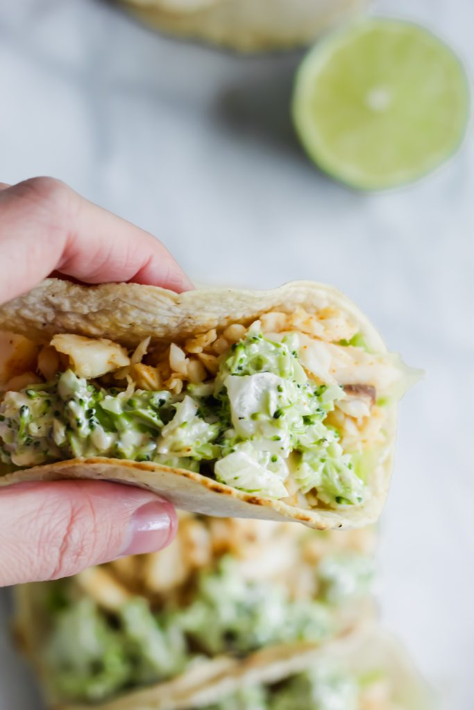 close up of hand holding a Spicy Fish Taco with Broccoli Slaw