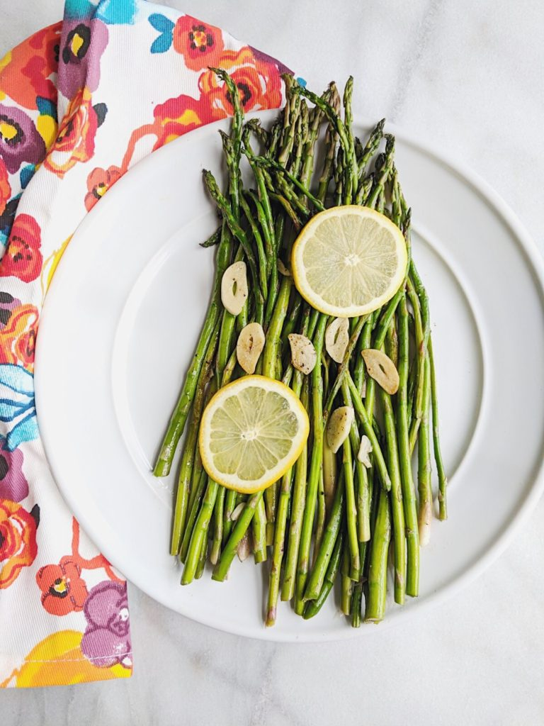 Easy Garlic Lemon Asparagus far away with floral towel under white plate