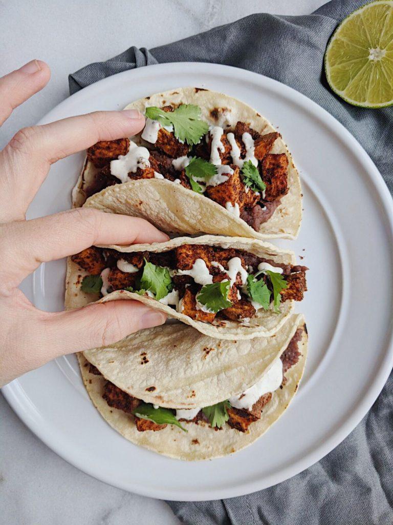 refried sweet potato tacos with lime crema holding a taco shot