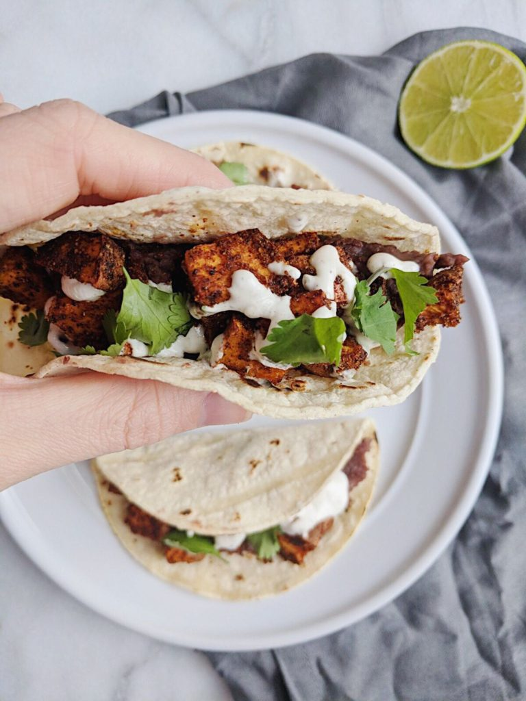 refried sweet potato tacos with lime crema holding close up