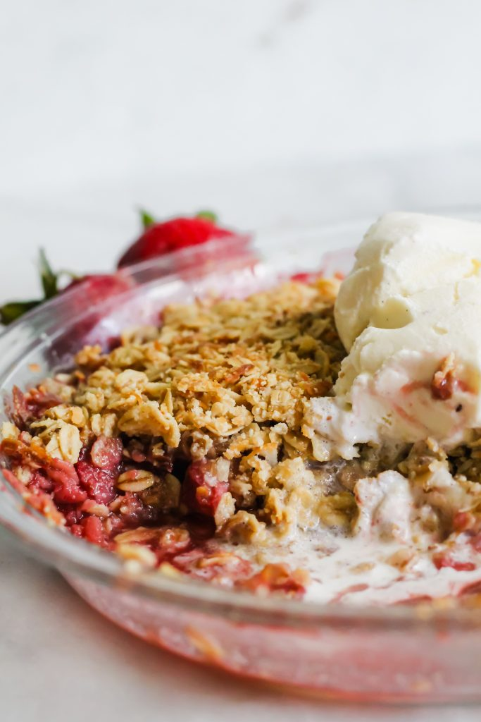 Strawberry Coconut Crisp in pan with melted ice cream