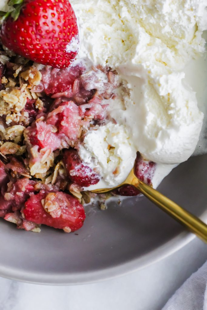 spoonful of Strawberry Coconut Crisp with melted ice cream