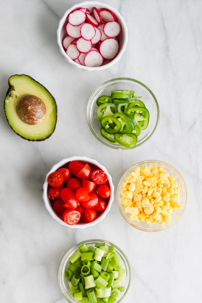 radish, avocado, jalapeno, corn, tomato and green onion in bowls