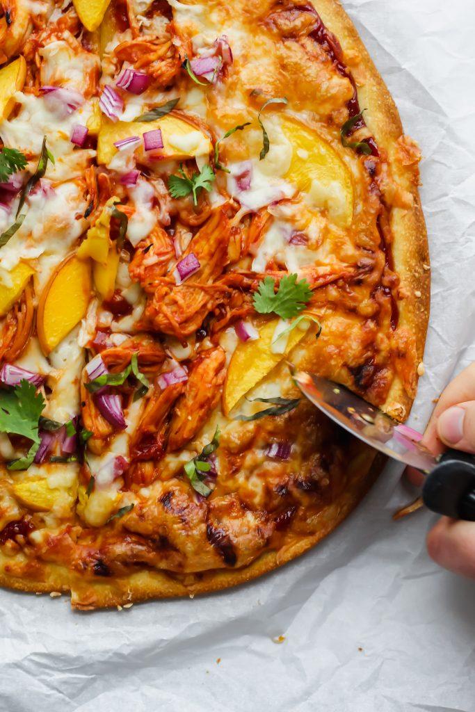 pizza cutter slicing Peach BBQ Chicken Pizza