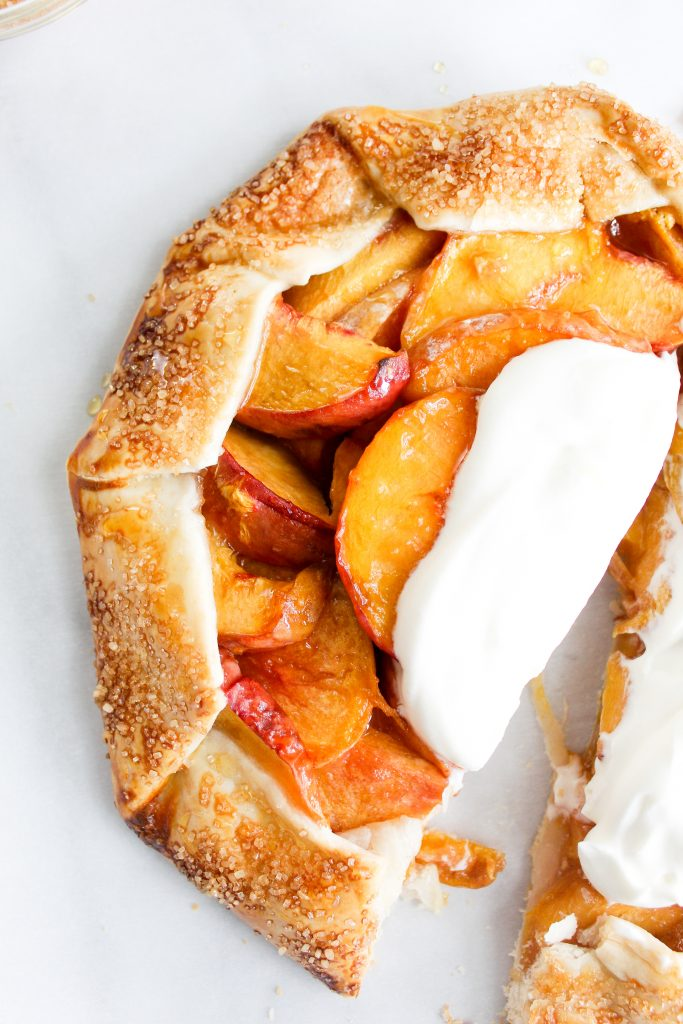 Rustic Honey Peach Galette with homemade whipped cream cut in half