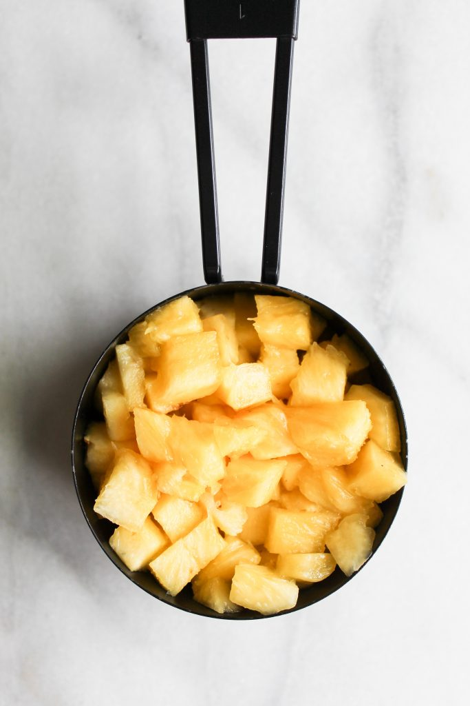 diced pineapple in a measuring cup