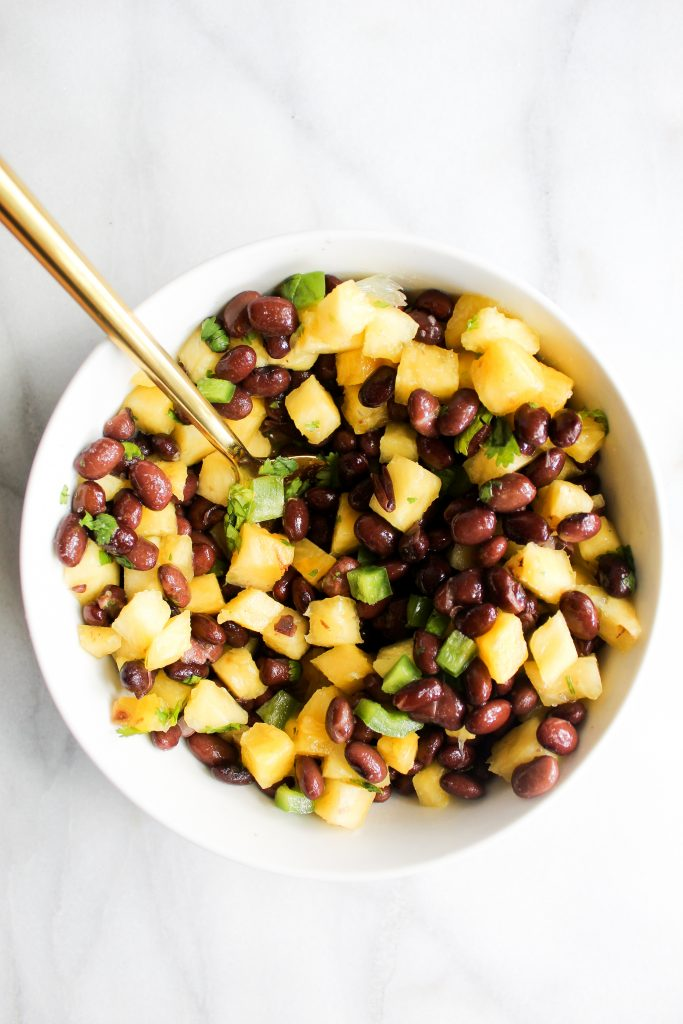 Pineapple Black Bean Salsa in a while bowl with a golden spoon