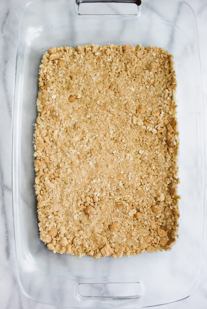 Apple Crumble Bars with Cinnamon Spice Glaze crust in glass pan