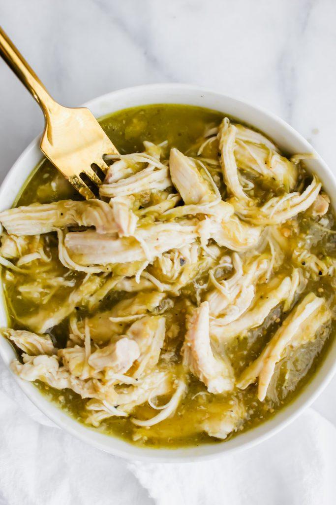2 ingredient salsa verde chicken in white bowl with gold fork