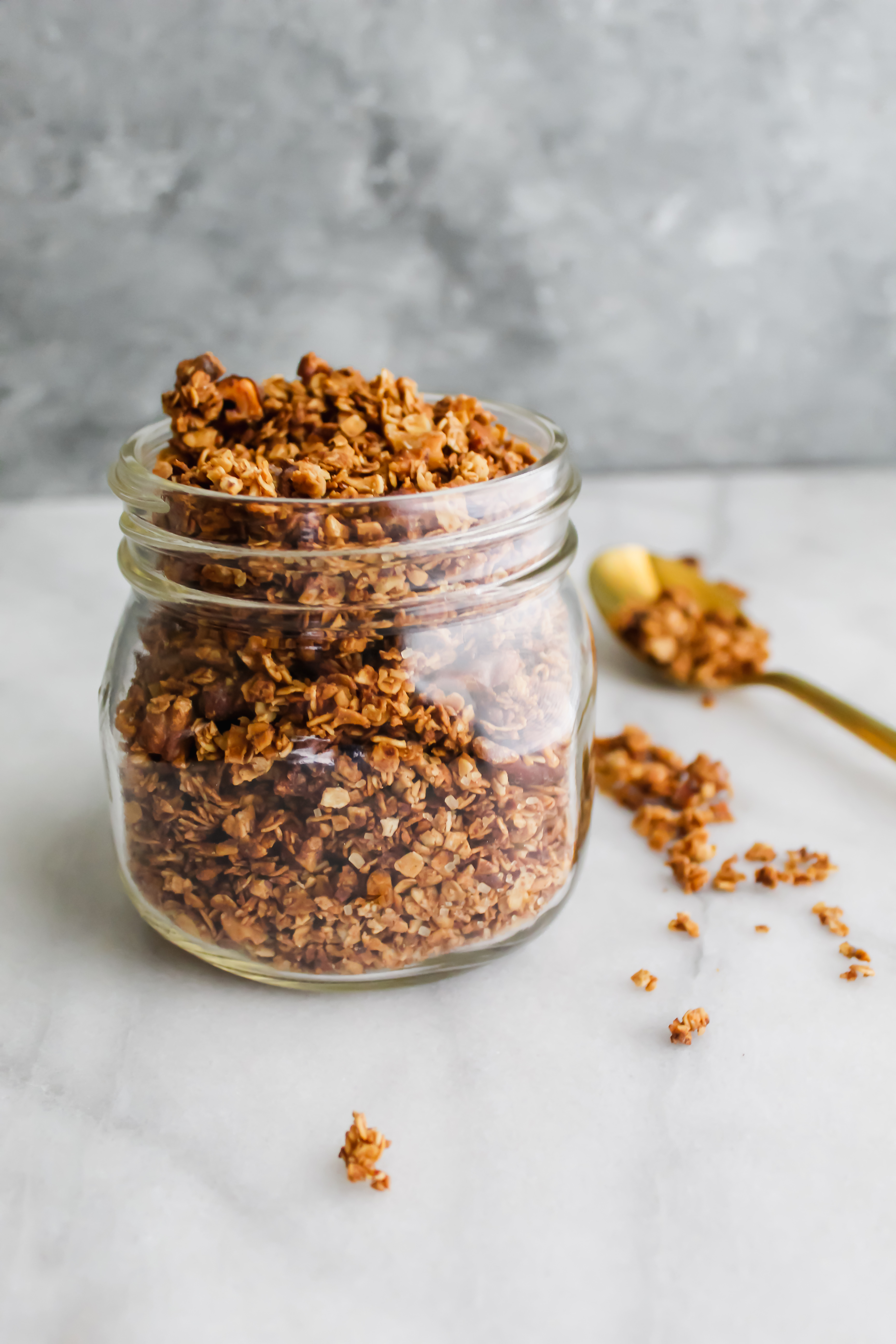 maple french toast granola in a mason jar with a gold spoon