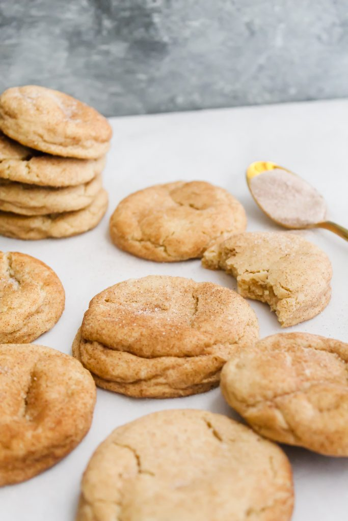 45 degree angle shot of Soft Chai Snickerdoodles with golden spoon full of chai spice sugar