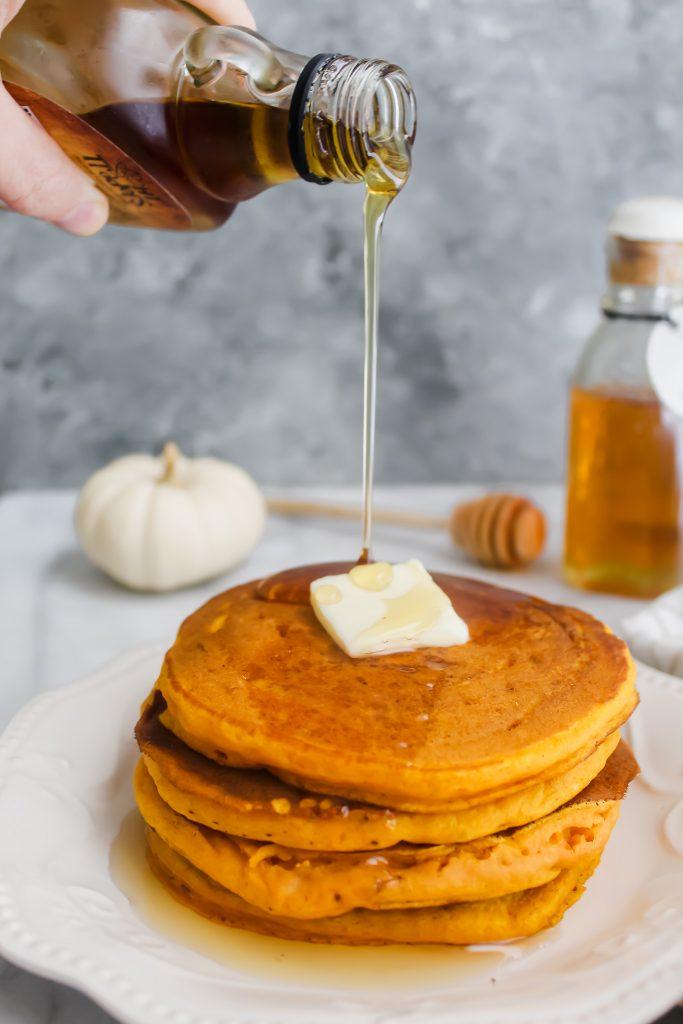 maple syrup pour on Honey Maple Pumpkin Pancakes