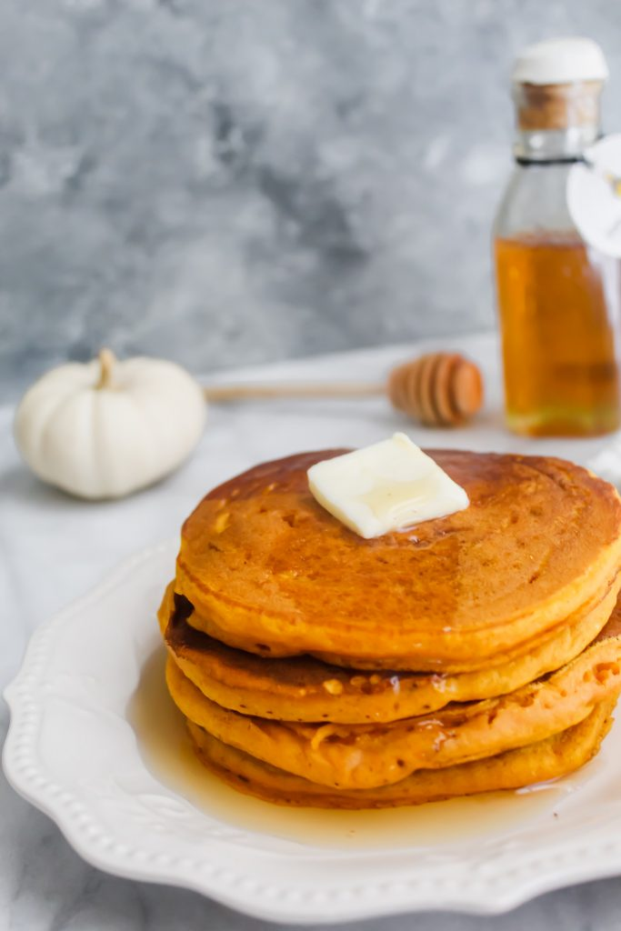 stack of Honey Maple Pumpkin Pancakes with butter and syrup on white plate