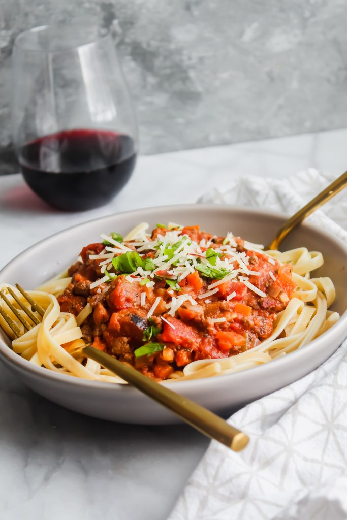 bowl of Pasta Bolognese with glass of red wine