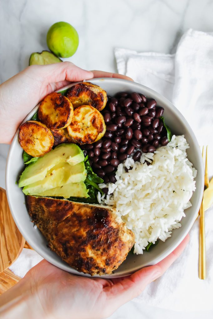 two hands holding Cuban Chicken and Black Bean Rice Bowls
