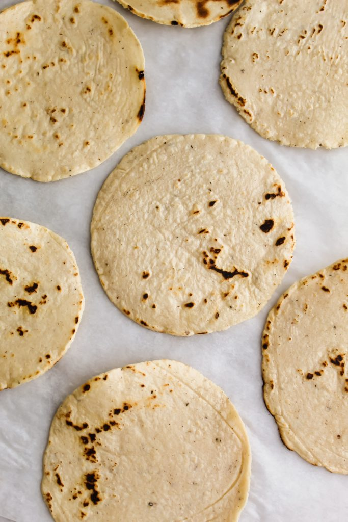 Homemade Corn Tortillas laying flat on parchment paper