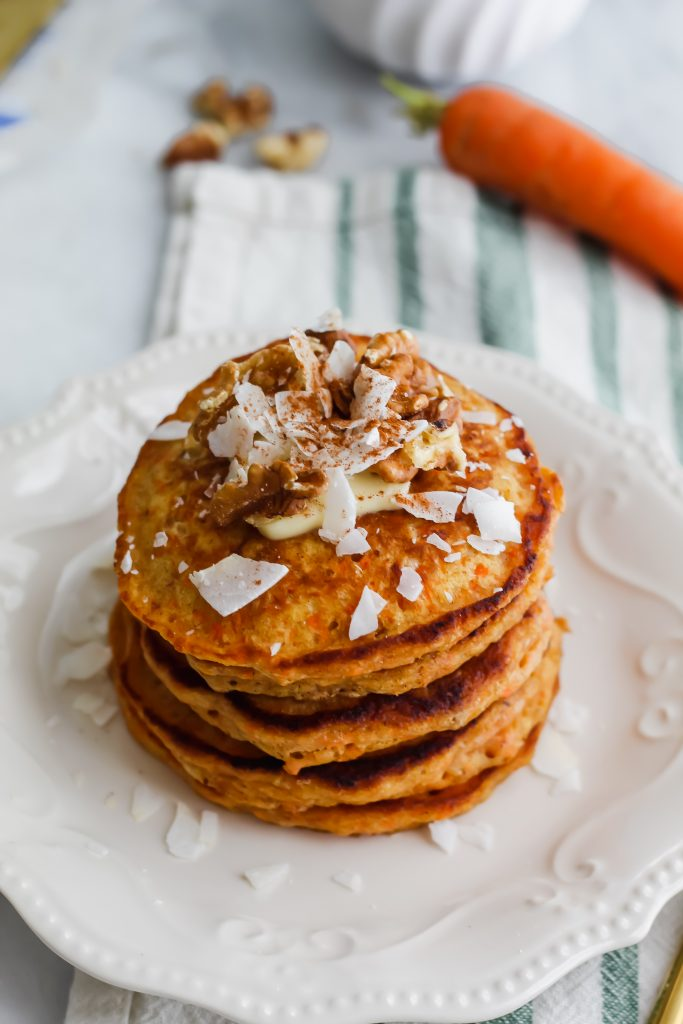 stack of Carrot Cake Pancakes with carrot in the background