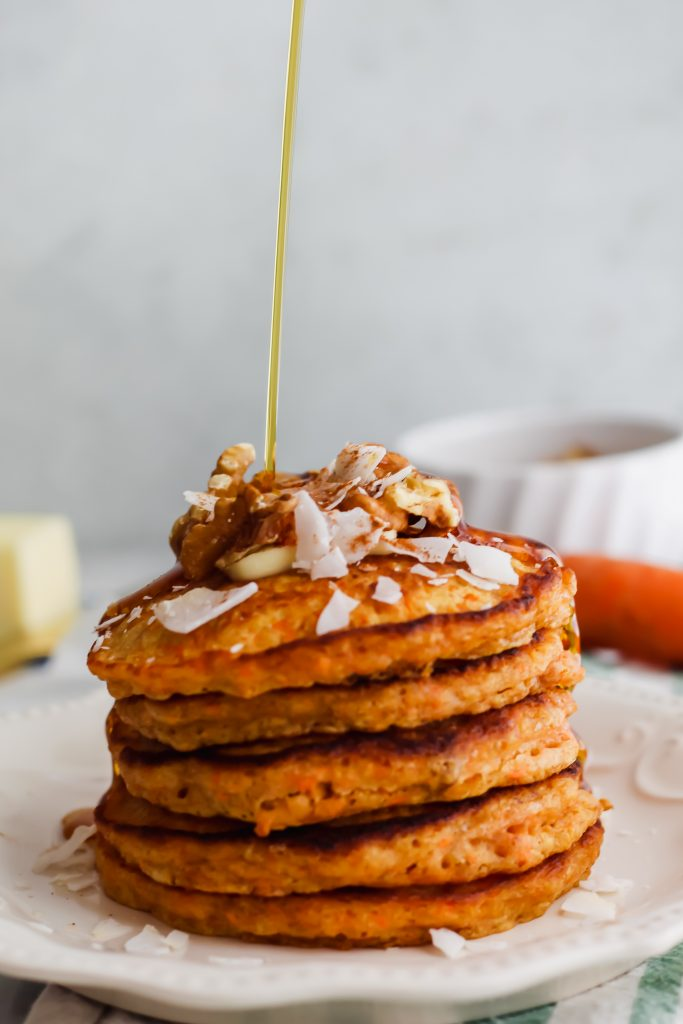 pouring maple syrup on stack of Carrot Cake Pancakes