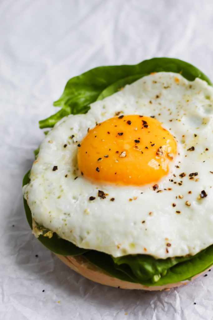 buttery fried egg sitting on spinach and bagel