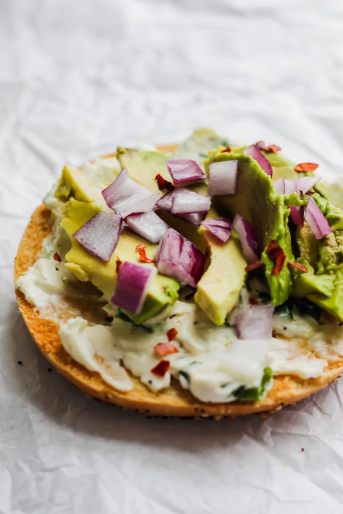 avocado and red onion on bagel