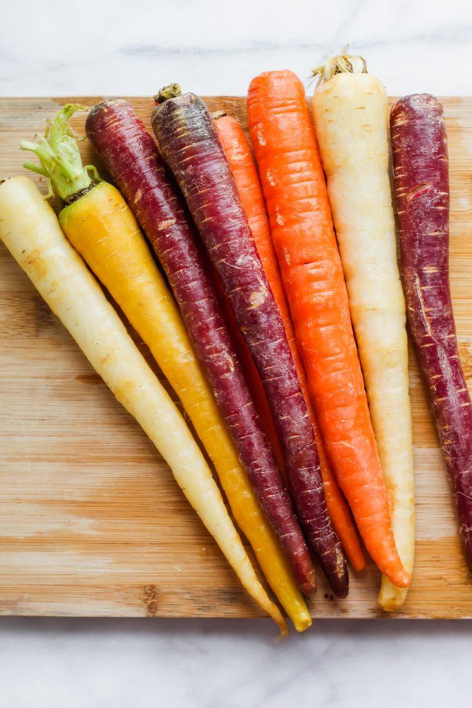 raw rainbow carrots on cutting board