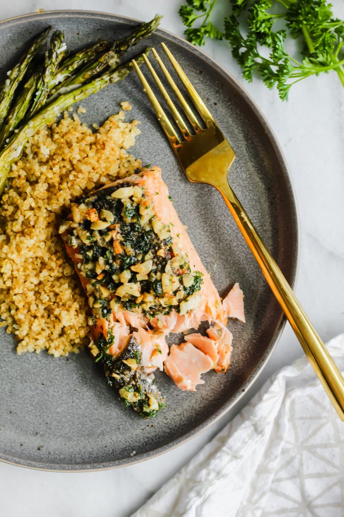 plate of Garlic Butter Pan Roasted Salmon with crispy quinoa and gold fork
