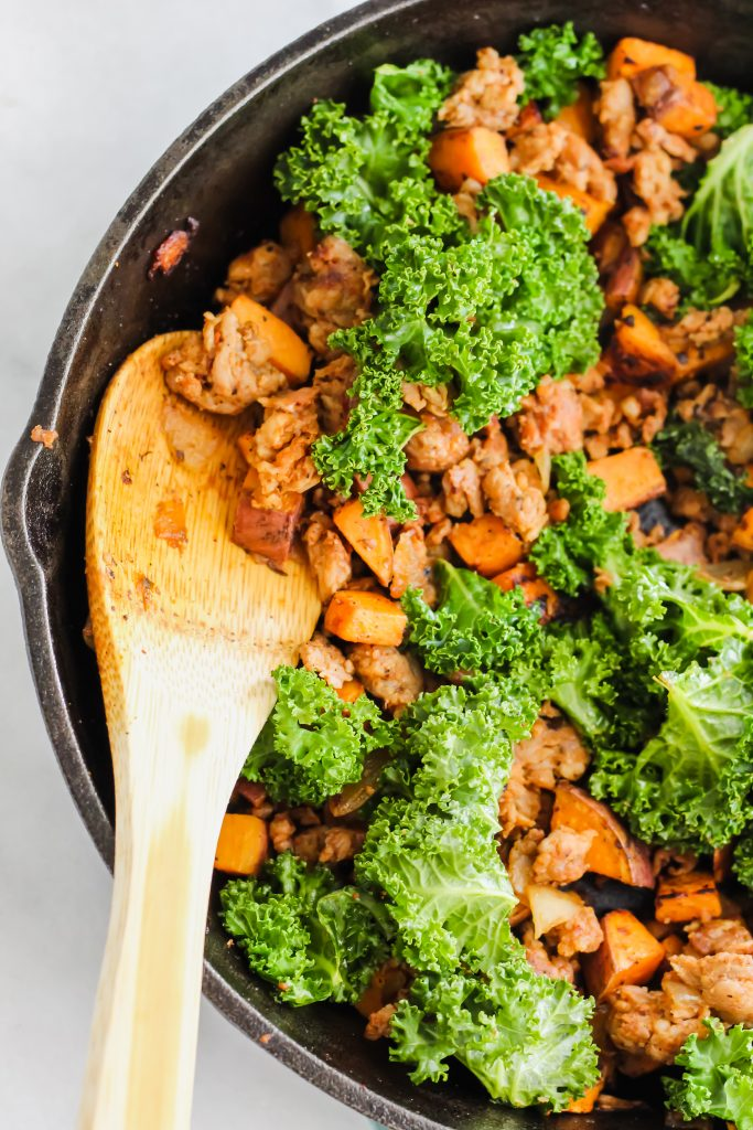 Chorizo, Kale and Sweet Potato Hash in the cast iron skillet with wooden spoon