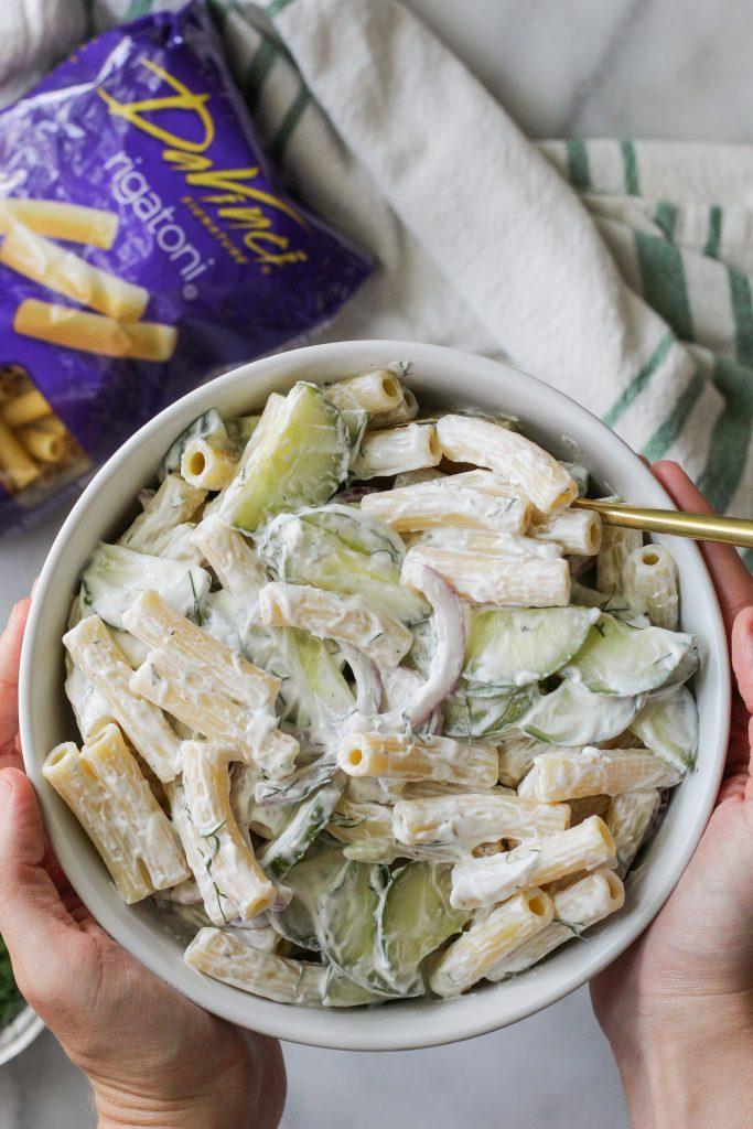 holding large bowl of Creamy Cucumber Pasta Salad