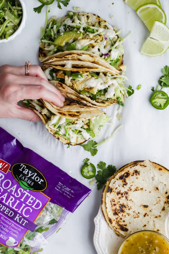 hand grabbing Roasted Garlic Green Goddess Tacos