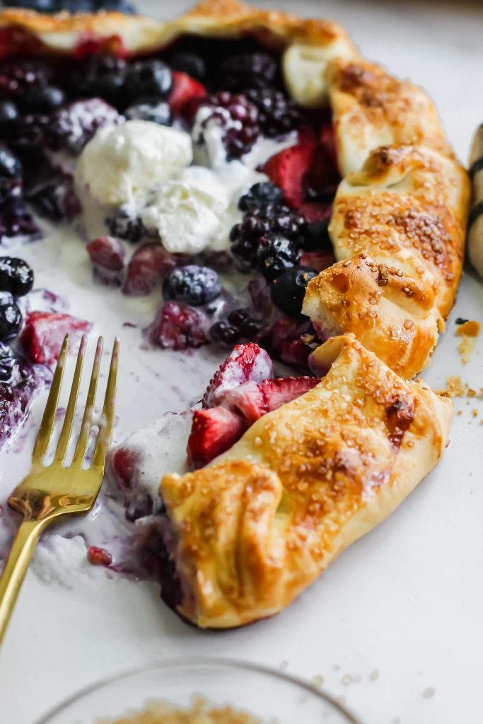 half eaten slice of Mixed Berry Galette with golden fork