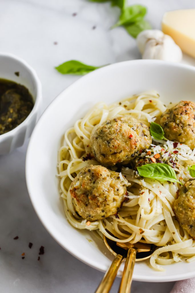 side angle of Chicken Pesto Meatballs on pasta with golden fork