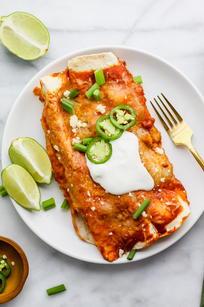 white plate of garnished enchiladas with golden fork